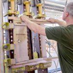 Der Mann baut die Holzkonstruktion des ZOE-Kirchenstuhls zusammen, die mit der Bank verbunden werden kann.