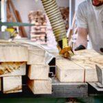 Sägen von Holz bei der Herstellung von Kirchenstühlen auf einem Bibelhalter für eine Kirchenbank.